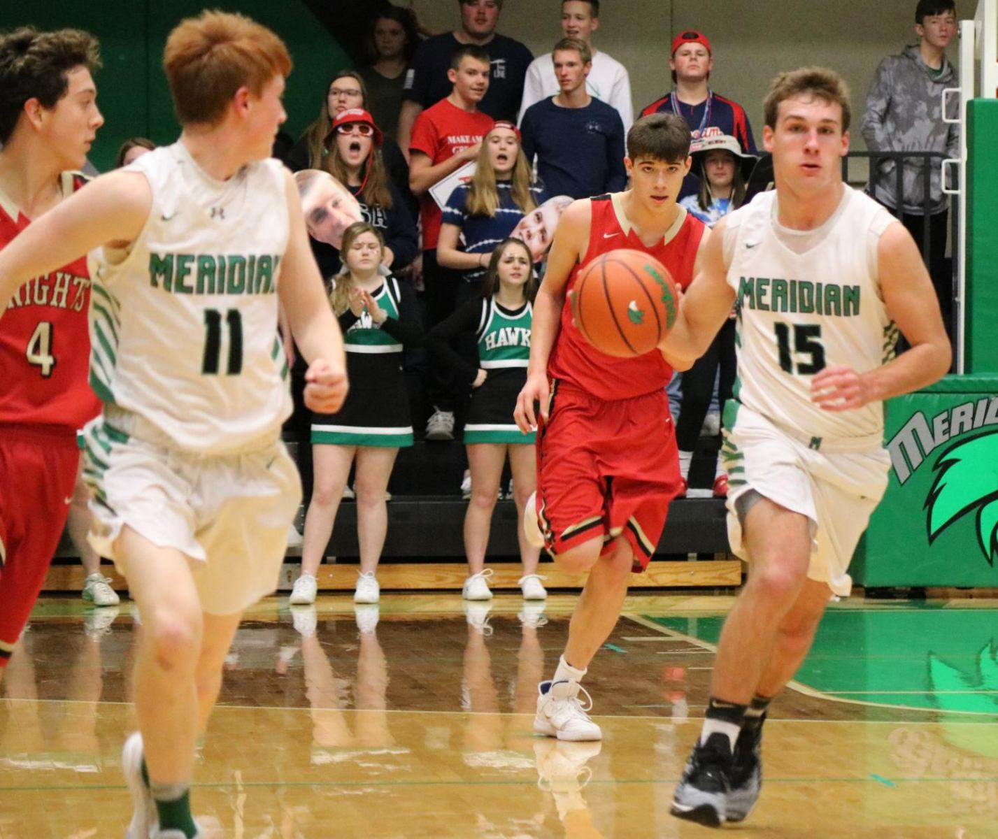 Jacobs Jones dribbles the ball then passes it to number 11 Riley Day.
