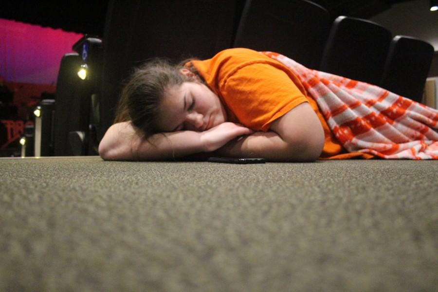 Freshman, Sydney Moore asleep on the job. Tired from late nights and exhaustion during the  last days before curtain call, the cast and crew become overwhelmed and rushed.