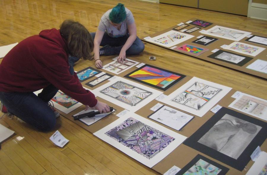 Surreal in every way. Sophomores Marley and Zoe Doering help set up and display the artwork from high school and middle school students.