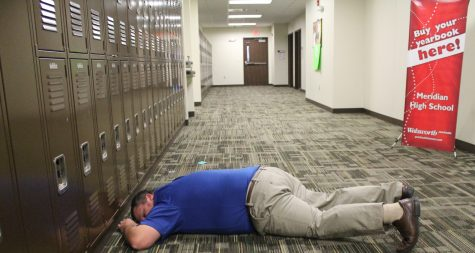 """Man down! Business and Technology teacher Phil Stielow gets """"shot"""" by Denna Williams during the ALICE simulation. The ALICE simulation was provided to Meridian 6-12 teachers on January 4, 2017 as a way to provide active shooter response training.    """"Being shot was quite a surprise,"""" says Stielow. """"As a teacher, you hope you never have to use ALICE training, but it does make you think more about being safe in extreme situations."""""""