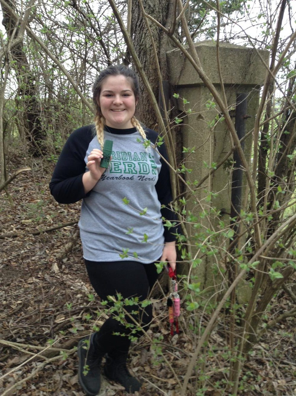 Found it! Sophomore Sydney Moore finding a hidden geocache after a long search.