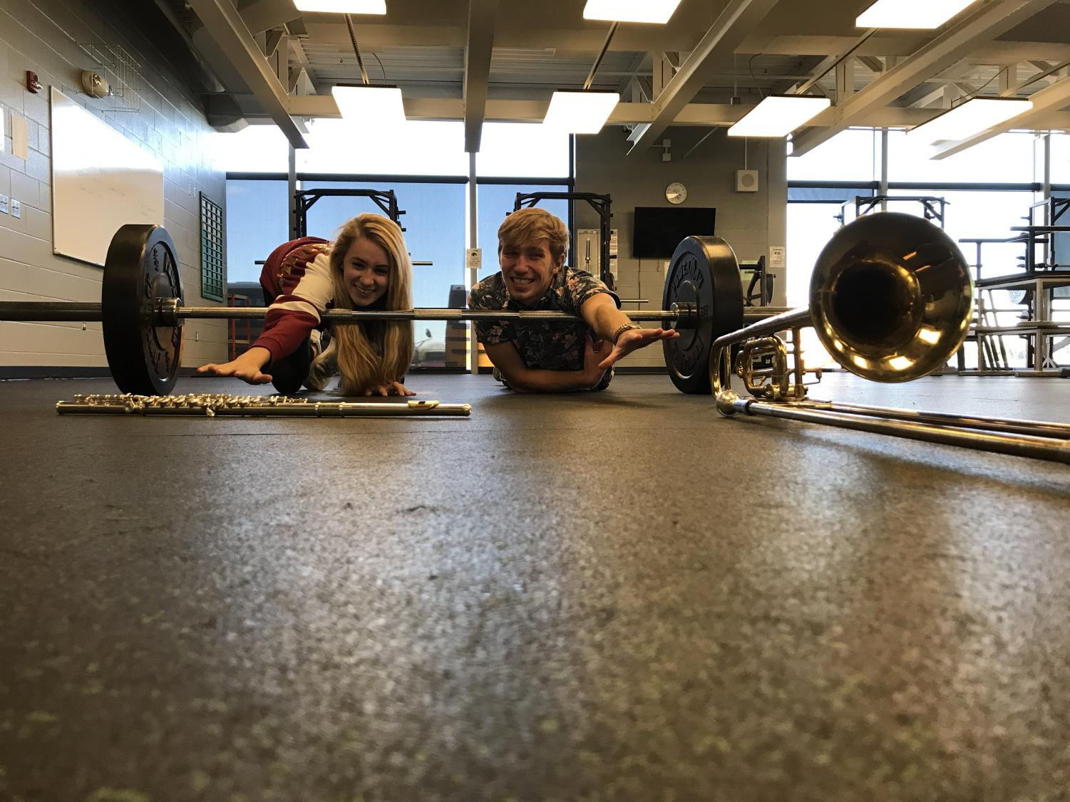 "Reach! Junior, Hannah Craft, and senior, Ian Carnahan, reach for their ability to play in the band their senior year as the weighted system holds them back. ""I put years of work into being a valedictorian,"