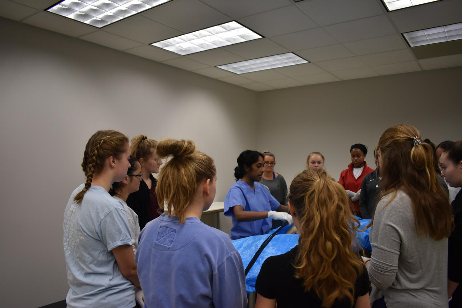 A group of students gather around a cadaver to learn its  medical history.