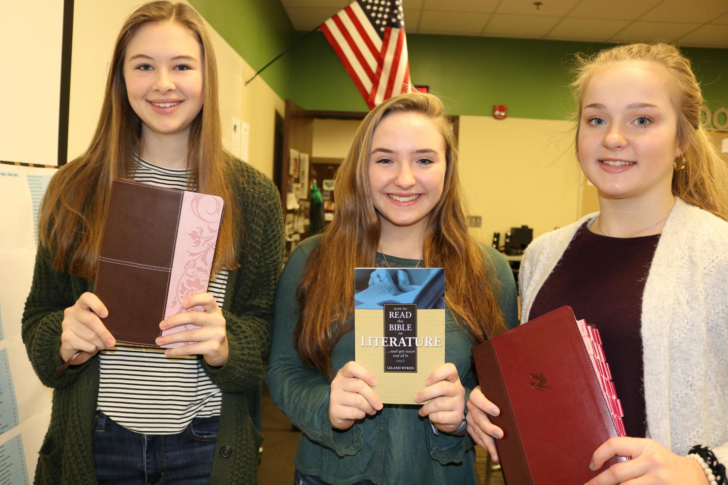 Emily Johnson, Lyric Greenwood and Audrey Wise from Meridian High School hold Bibles that they will use in class.