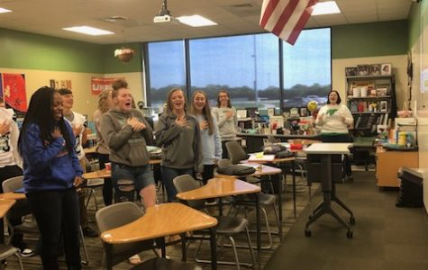Students in Sheila Moore's fifth hour Honors English 2 class stand and sing the Fergie version of the National Anthem during fifth hour.