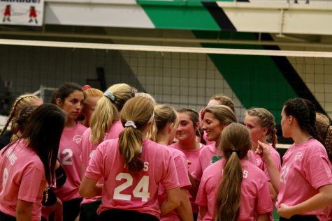 "Meridian Volleyball in a timeout during their pink night game against Warrensburg-Latham. ""[Hendricks] encourages us to work our hardest and never give up. She keeps our head high and helps us be the best we can,"" said Lyric Greenwood, junior."