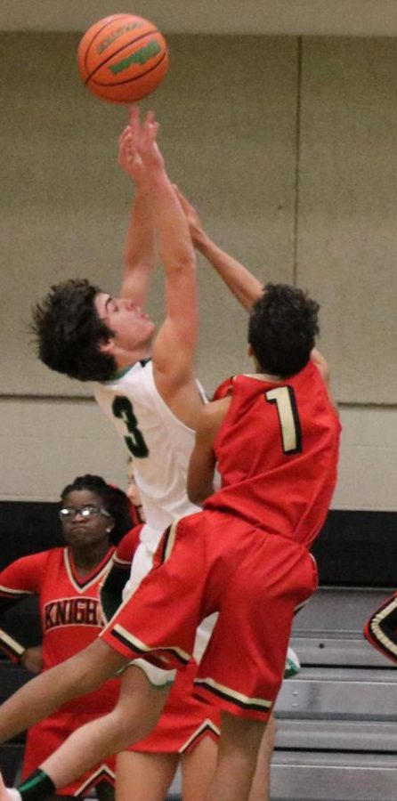 Tyler Ward,  shoots the ball, but gets blocked by number 1 on the ALAH JV Boys Basketball team.