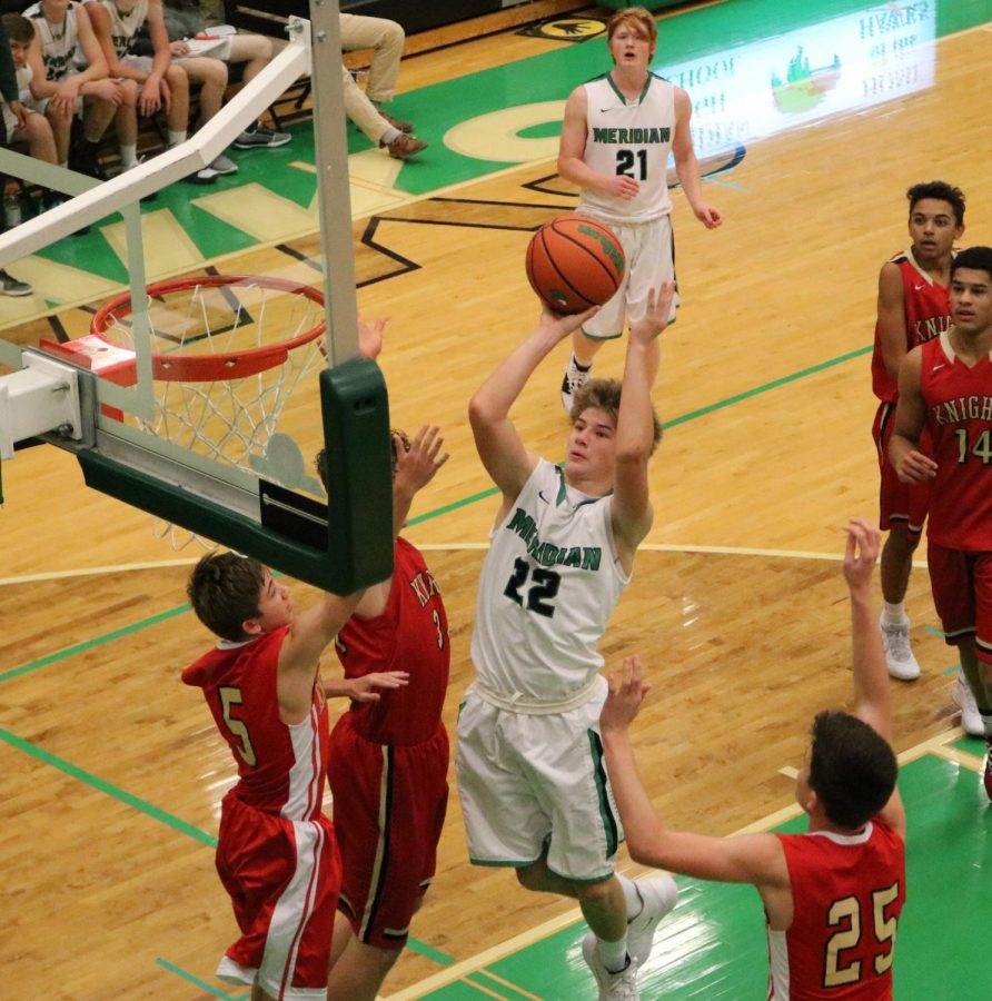 Lucas Clapp rushes for the layup while confronting three opposing players.