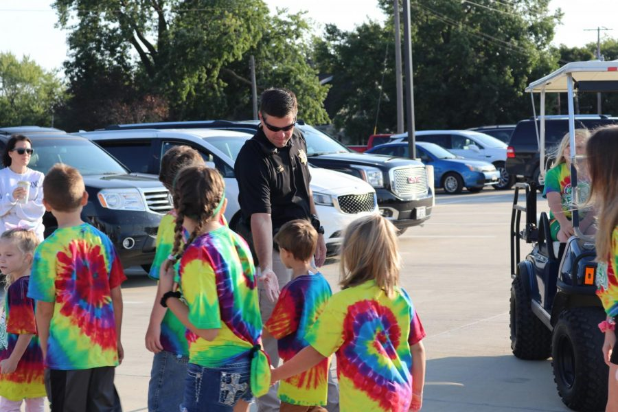 Blue Mound police chief, Chad Lamb, high fiving students as they leave for their walk-a-thon fundraiser walk around Blue Mound. The elementary school does this fundraiser to help fund things throughout the school year for the students.