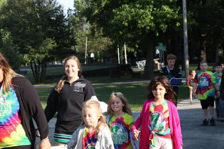 Senior, Ella Snow walks with second grade during annual walk-a-thon fundraiser. The elementary school does this fundraiser to help fund things throughout the school year for the students.