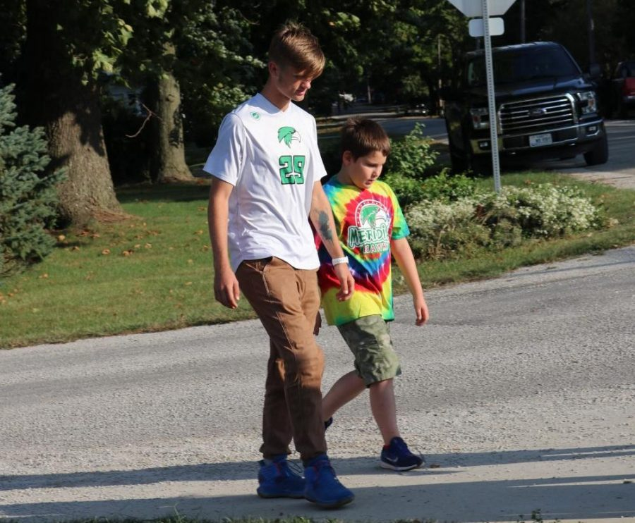 Senior, Cole Boehm walks with kid during the annual walk-a-thon fundraiser around Blue Mound. The elementary school does this fundraiser to help fund things throughout the school year for the students.