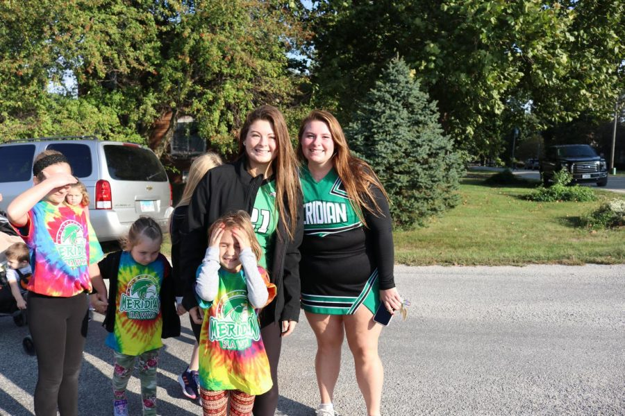 Cheer Seniors, Peyton Latham and Heather Crackel pose with students at the end of the the walk around Blue Mound. The elementary school does this fundraiser to help fund things throughout the school year for the students.