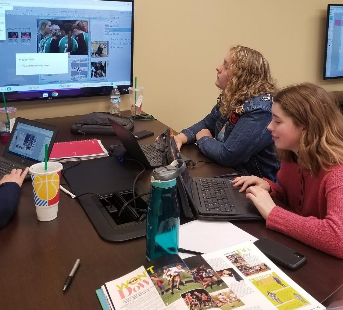 Delaney Jones and Ellie Fitzpatrick work on a spread during a visit from Mike Taylor. Jones is the 2021 business manager and Fitzpatrick is the copy writer.