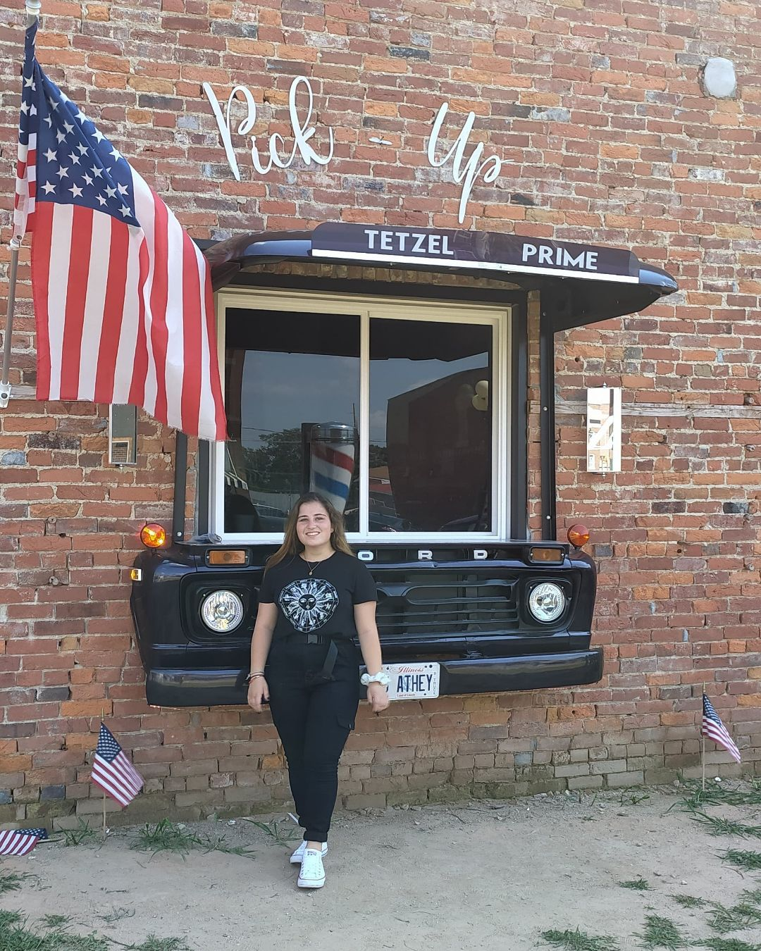 Victoria Muller posing with American flag. Photo taken by her host mother in Casey, Illinois.