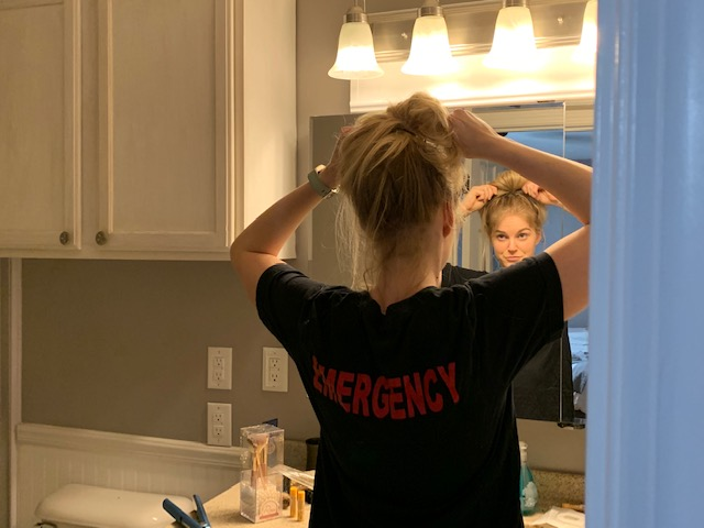 Karma Lockwood, still in her work clothes, puts her hair up in a bun. Lockwood is a registered nurse and works in an emergency room.