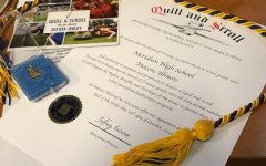 Several Quill and Scroll items are displayed, including the cord Le Cates will wear at graduation.
