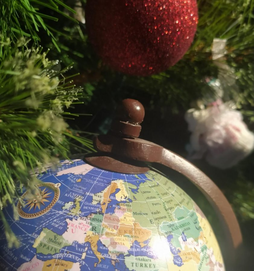 Zoom in of the European drawing of a globe in front of a Christmas tree. Christmas is celebrated differently throughout the world.