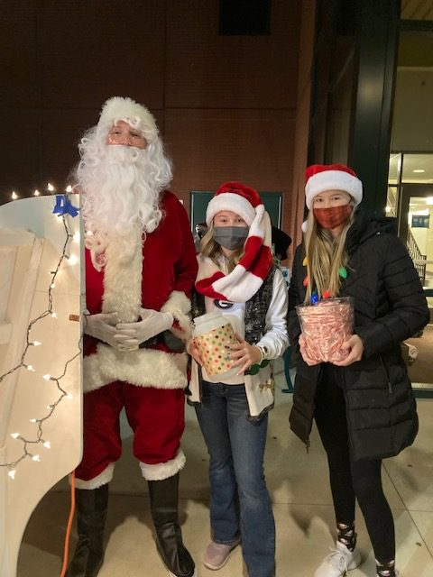 Colin Heidemann, Audrey Wise, and Emily Johnson stand next to the big white sleigh that the toys were collected in. Heidemann enjoyed  greeting the cars.