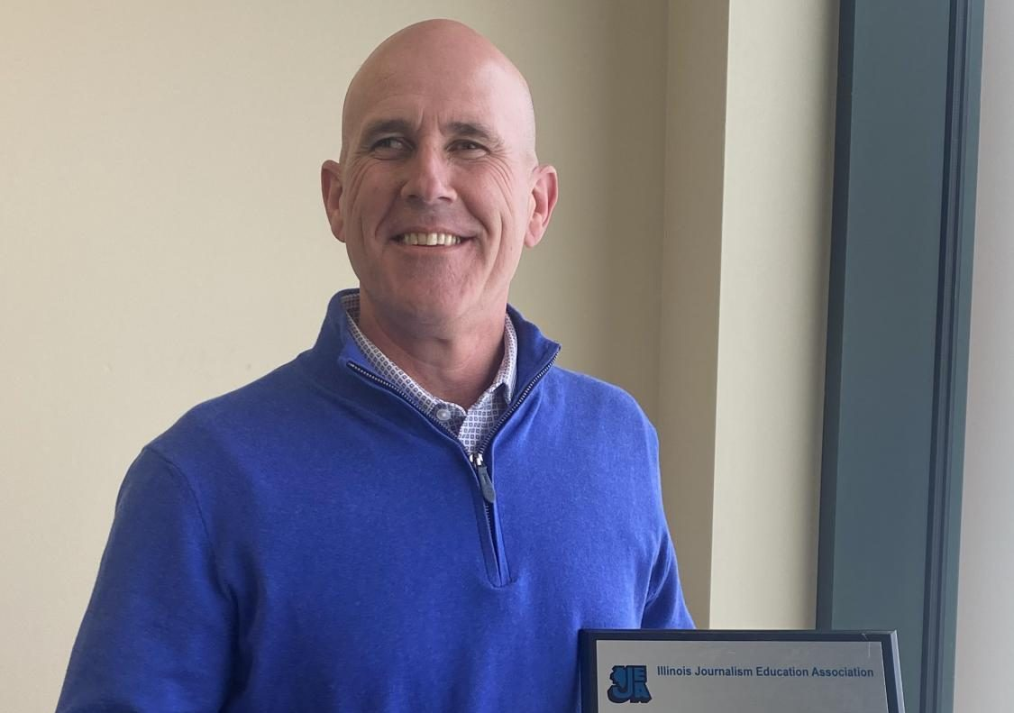 Principal Eric Hurelbrink holds his award in his office. Hurelbrink was awarded the IJEA (Illinois Journalism Education Association) Administrator of the Year for 2020 and  only 12 people in the past 25 years have received this award.