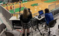 Hallie Gates and Reagan Hunt live stream a boys' basketball game as members of the media club. The members sign up for different events, they also set-up and take-down all the equipment.