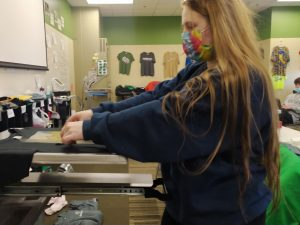 Alyssa Anglin makes a shirt for the 5th birthday of a little boy in Entrepreneurship. She is printing a pattern on a shirt with this compressing machine.