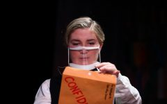 Wadsworth, played by senior Hallie Gates, opens a confidential folder.  The clear masks were chosen so the audience could see the actor's facial expressions.