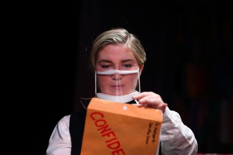 Wadsworth, played by senior Hallie Gates, opens a confidential folder.  The clear masks were chosen so the audience could see the actor