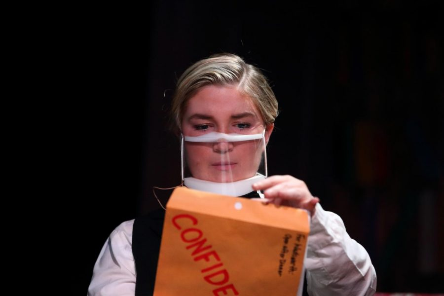 Wadsworth, played by senior Hallie Gates, opens a confidential folder.  The clear masks were chosen so the audience could see the actors facial expressions.